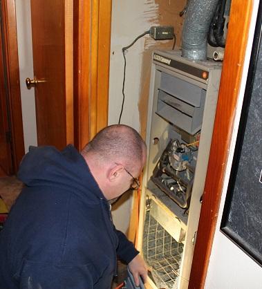 Fenix technician working on an old broken furnace in a Wichita, KS home